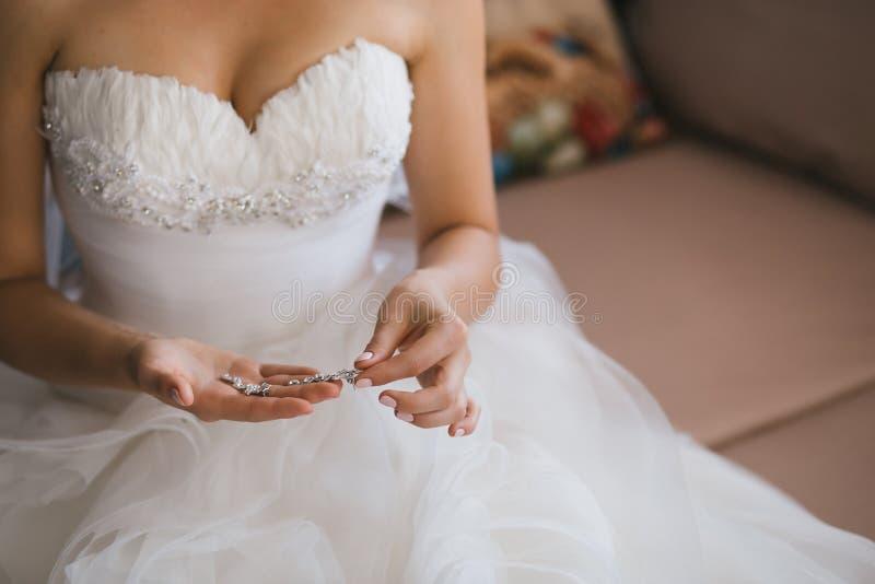 Невеста держа серебряные серьги Нежные руки с ювелирными изделиями стоковая фотография