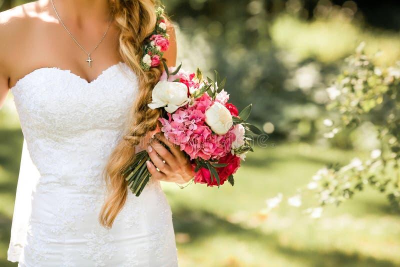 Невеста держа чувствительный букет замужества Красивый солнечный день в парке стоковые фото
