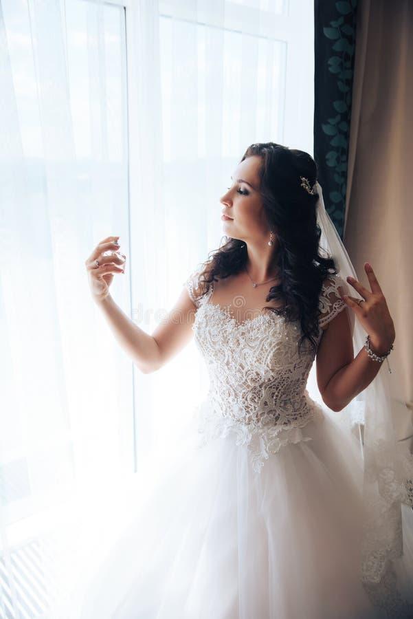 Невеста держит духи, стоя на окне стоковое изображение