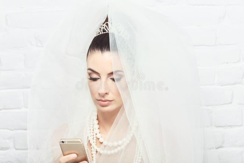 Невеста используя мобильный телефон стоковое изображение rf
