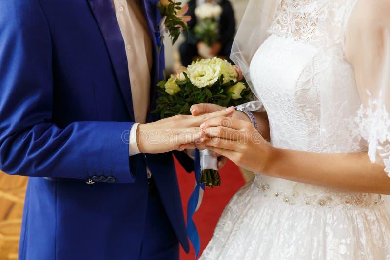Невеста кладя кольцо на палец groom стоковая фотография