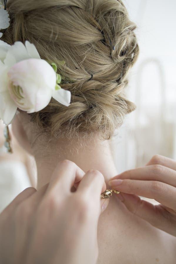 Невеста, который нужно попробовать извлечь ожерелье после свадьбы стоковое фото