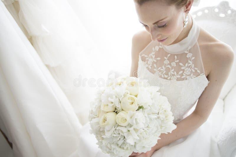 Невеста, который нужно сидеть на софе имеет букет стоковые изображения rf