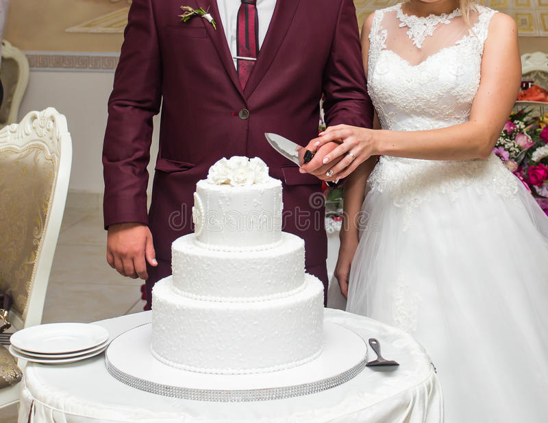 Невеста красоты и красивый groom режут свадебный пирог стоковое изображение