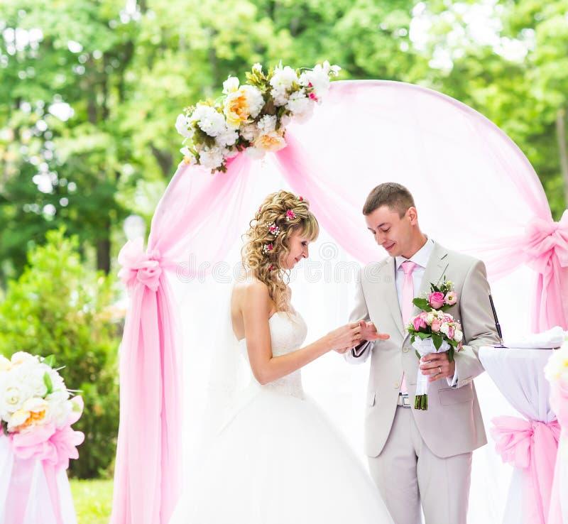 Невеста кладя кольцо на палец groom во время свадебной церемонии стоковые фотографии rf