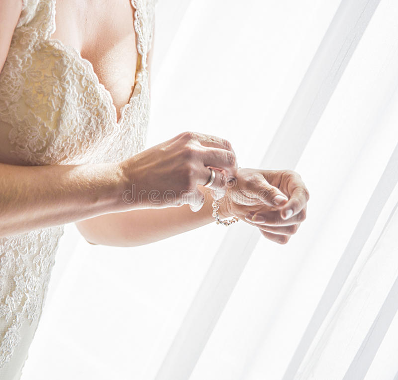 Невеста кладя на браслет стоковые фотографии rf