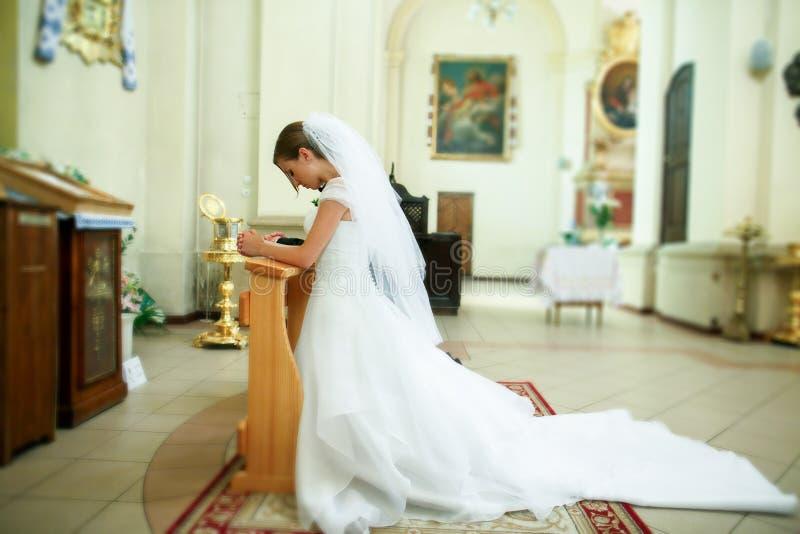 Невеста молит на коленях стоя в фронте значка в стоковое изображение rf