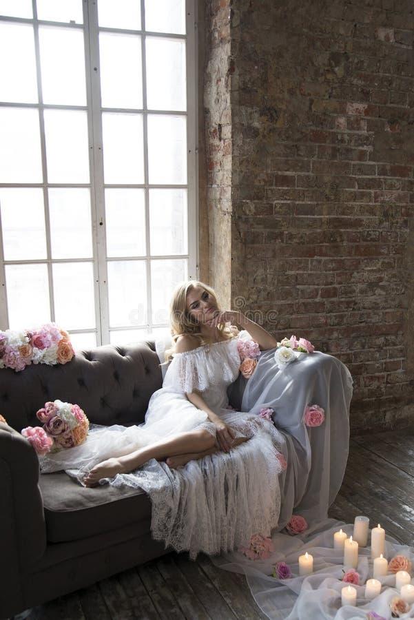 Невеста на винтажной софе с цветками и свечами стоковые фотографии rf