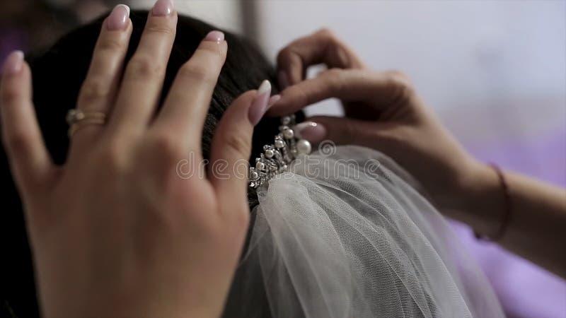 Невеста на салоне парикмахерских услуг делая подготовки свадьбы, руки стилизатора касаясь ее волосам r Закройте вверх для женщины стоковые изображения