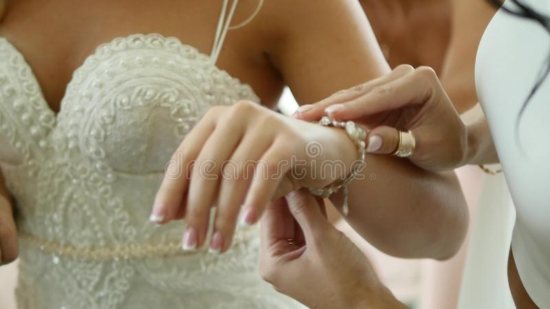 Невеста носит ювелирные изделия свадьбы, положила браслет на запястье руки стоковая фотография rf