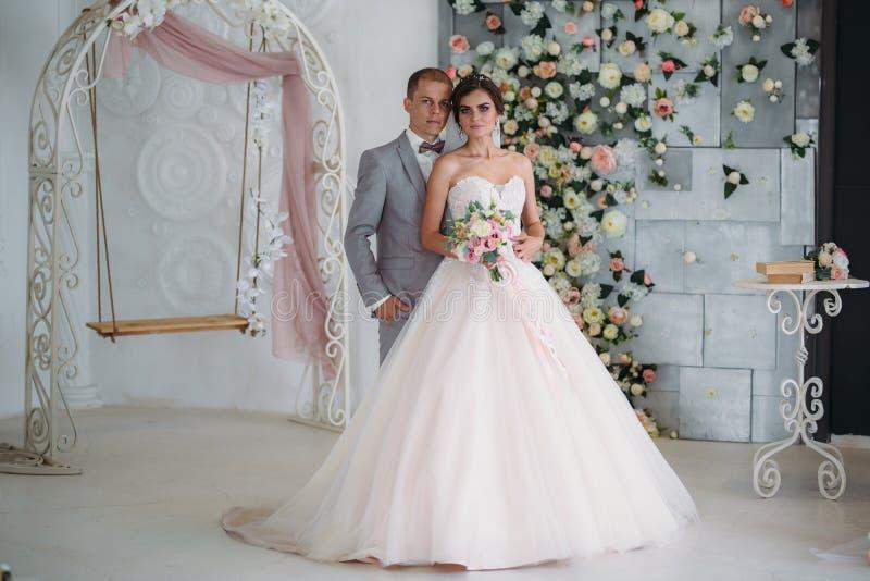 Невеста обнимает groom и держит букет цветков в ее руках Красивая пара новобрачных на день свадьбы стоковые изображения
