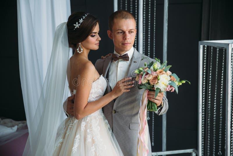 Невеста обнимает groom и держит букет цветков в ее руках Красивая пара новобрачных на день свадьбы стоковые изображения rf