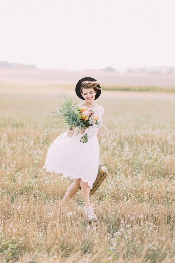 Невеста одетая годом сбора винограда идет весной поле Она держит красочный букет и носит ретро стоковая фотография