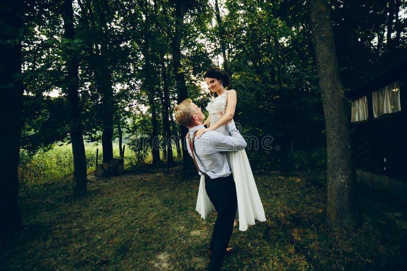 Невеста поднятая Groom в его оружиях стоковое фото