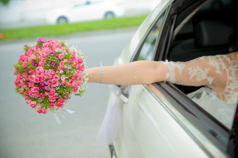 Невеста приняла вне розовый букет цветка из автомобиля девушка невесты идет к wedding автомобилям и развевать с букетом из ее T стоковые изображения