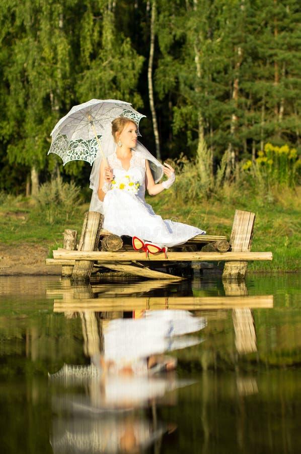 Невеста при зонтик сидя на мосте стоковые изображения rf