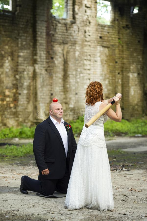 Невеста пробует ударить яблоко от для того чтобы выхолить голову с бейсбольной битой стоковое фото