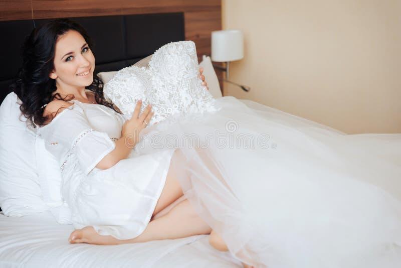 Невеста сидит на кровати и держит платье свадьбы в руках стоковые изображения rf