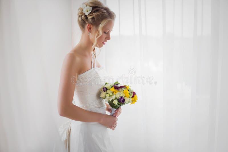 Невеста смотря вниз на ее букете свадьбы стоковая фотография rf