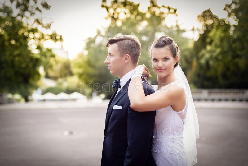 Невеста стоя за groom и смотря камеру стоковые изображения