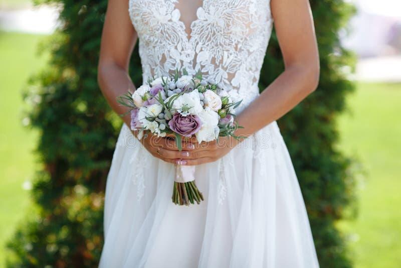Невеста стоя на зеленой предпосылке и держа букет фиолетовых цветков, белых цветков и растительности с пастелью стоковое фото