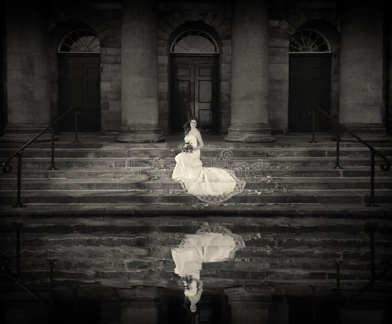 Невеста с свадьбой цветет букет в белом платье с стилем причёсок и составом свадьбы Усмехаясь женщина в платье свадьбы ждать gr стоковая фотография rf