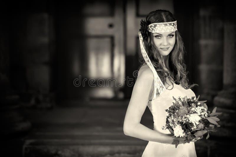 Невеста с свадьбой цветет букет в белом платье с стилем причёсок и составом свадьбы Усмехаясь женщина в платье свадьбы ждать gr стоковое изображение rf