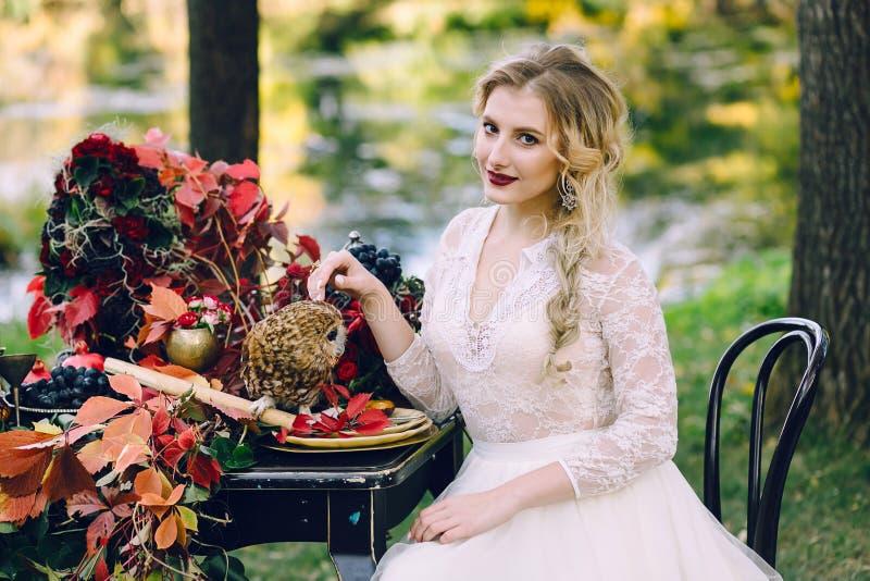 Невеста с сычом Красивая усмехаясь невеста сидит около, который служат wedding таблицы с красными листьями осени стоковая фотография rf