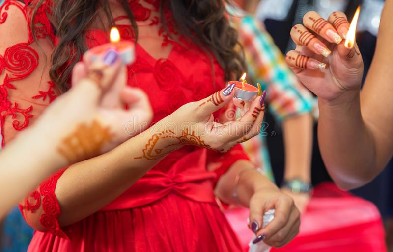 Невеста украшенная с декоративным подсвечником в ее руках и знаке держит свечу в ее руке на заднем плане снаружи стоковые изображения rf