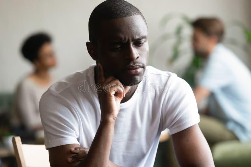 Нежеланный одинокий черный мужчина чувствует боль, сидя один стоковое изображение