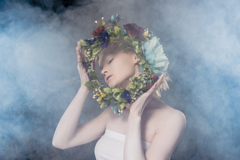 нежная девушка с белым макияжем держа флористический венок стоковое фото rf