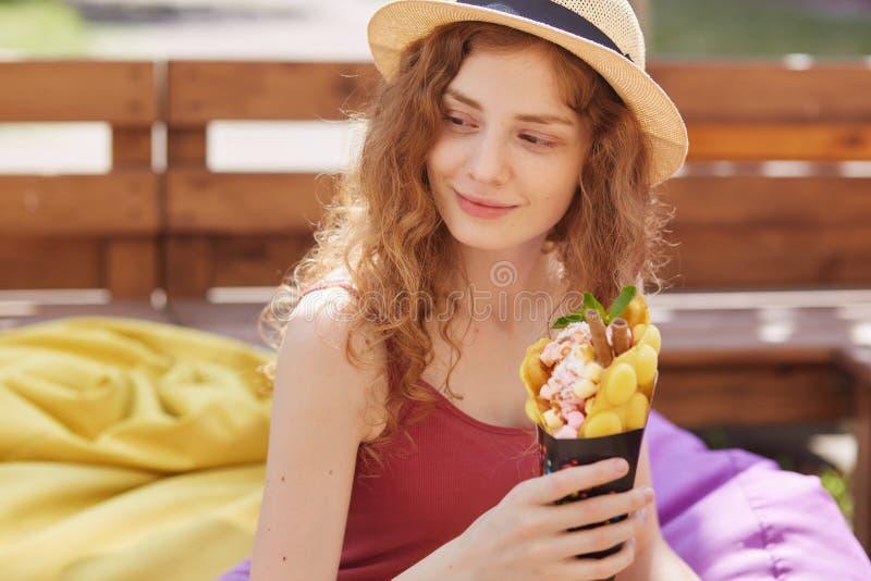 Нежная прелестная красивая маленькая девочка смотря в сторону, тратящ время самостоятельно снаружи, держащ десерт в обеих руках,  стоковые изображения
