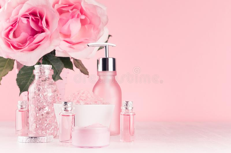 Нежная girlish одевая таблица с цветками, продуктами косметик - подняло масло, соль для принятия ванны, сливк, духи, полотенце хл стоковые фото