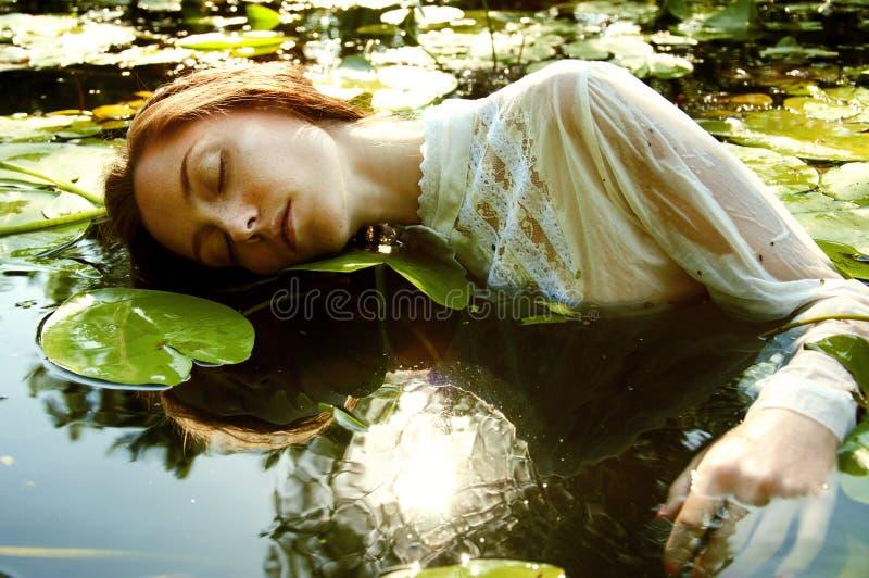 Нежное заплывание молодой женщины в пруде среди лилий воды стоковые фото