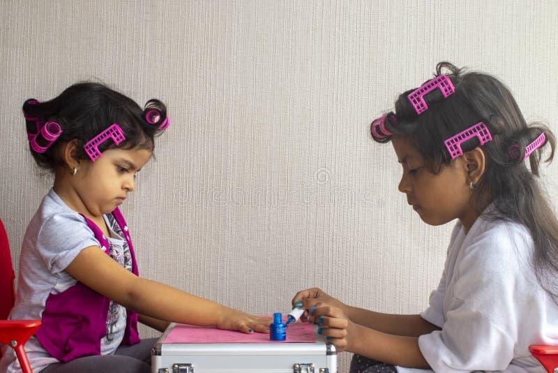 Нежные девушки играя ногти стоковые фото