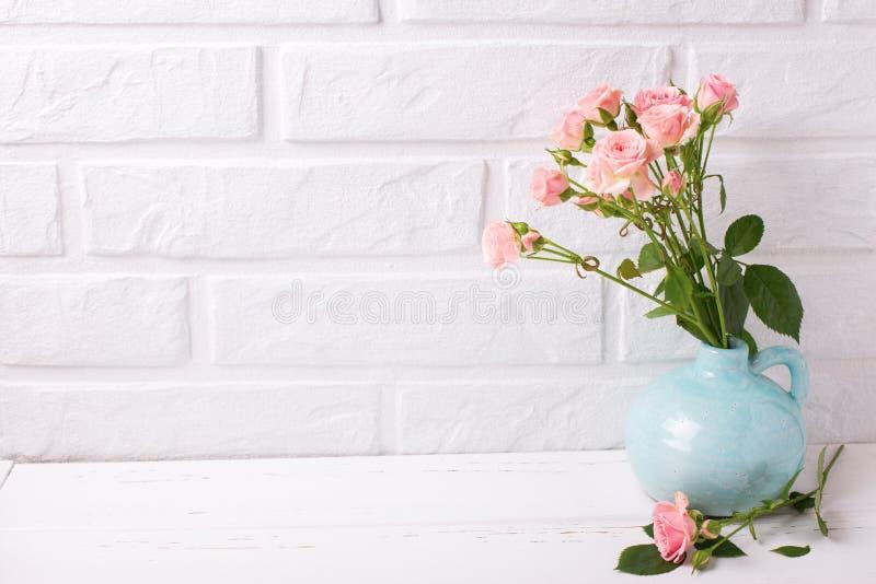 Нежные розовые розы цветут в голубой вазе на белом деревянном backgro стоковое фото