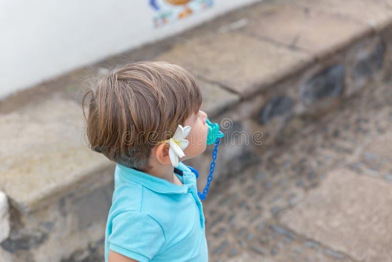 Нежный мальчик одетый в сини с pacifier, имеет белый цветок на его правом у стоковые фотографии rf