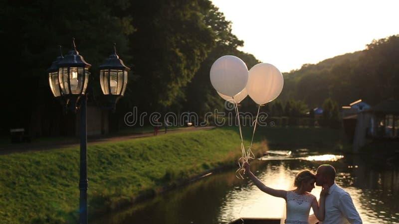 Нежный момент счастья и влюбленности Silhoettes молодых красивых пар свадьбы при воздушные шары обнимая на мосте акции видеоматериалы