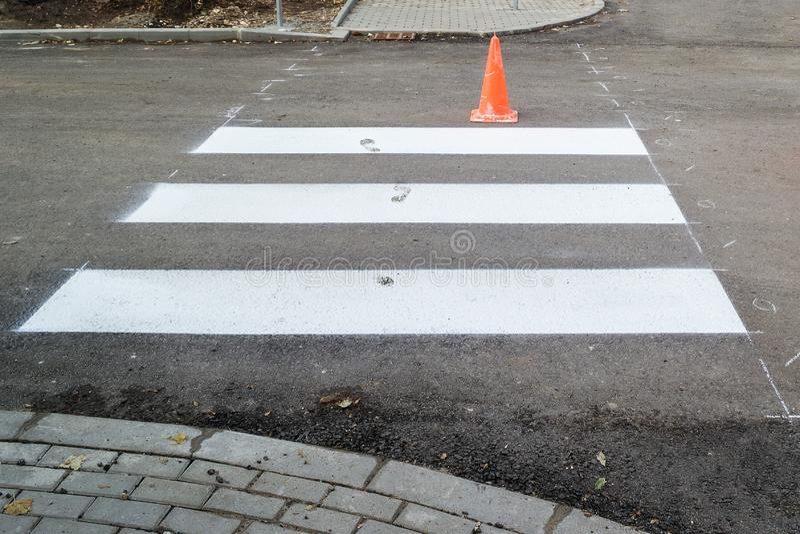 Незаконченная дорожная разметка на пешеходном переходе через дорогу Человеческие следы ноги на влажной краске дорожной разметки стоковые изображения