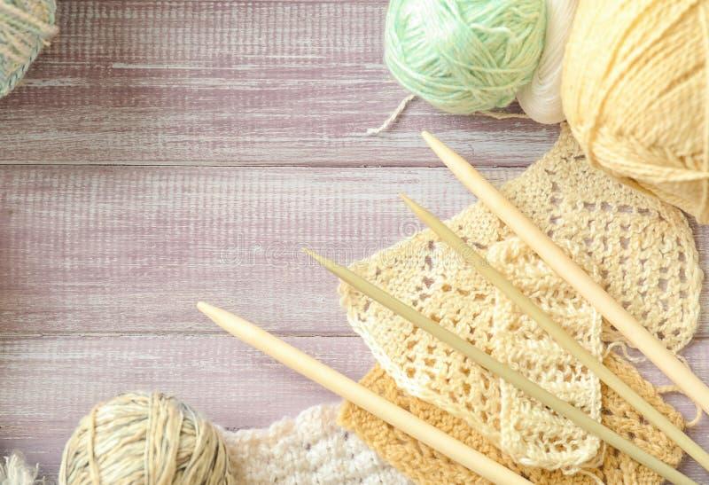Незаконченные вязать одежды с иглами на деревянном столе стоковое изображение rf