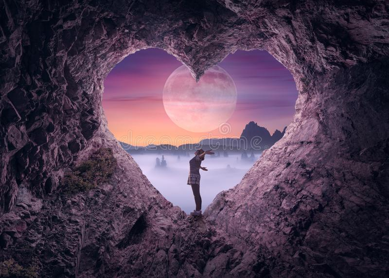 Незамужняя женщина в пещере формы сердца к идилличному пейзажу стоковые изображения rf