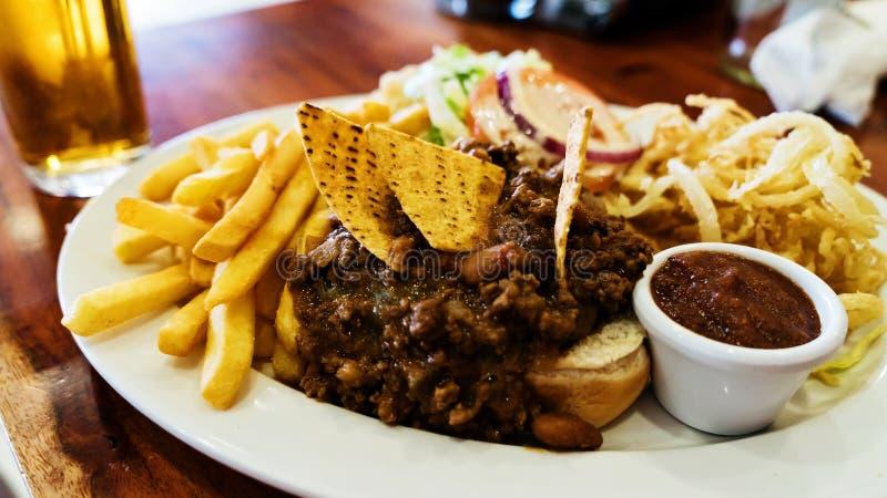 Нездоровая еда с мексиканскими обломоками nacho нагрузила с говядиной, сыром, фраями, кольцами лука стоковое изображение