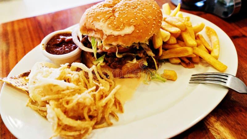 Нездоровая еда с мексиканским nacho откалывает, бургер говядины, нагруженный с сыром, фраи, кольца лука стоковые фото