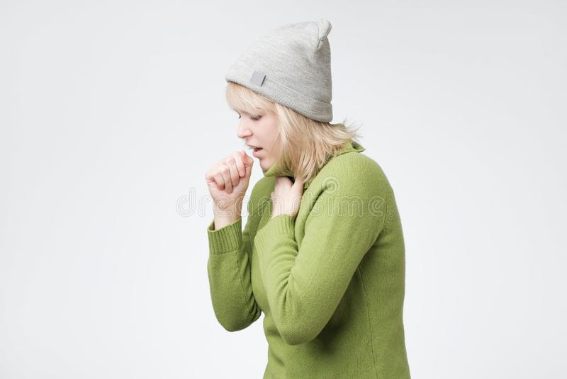 Нездоровая молодая белокурая женщина кашляя много, страдающ с кашлем, имеет боль в груди стоковые фото