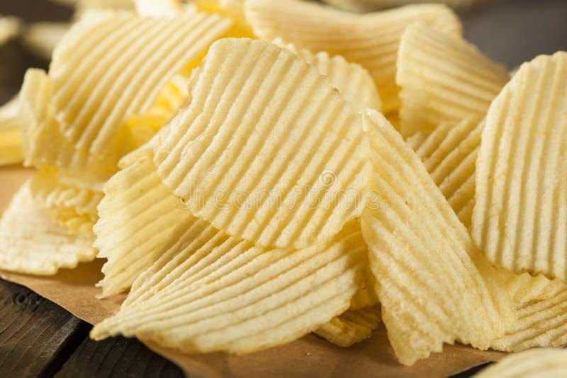 Нездоровые картофельные стружки отрезка Crinkle стоковое фото