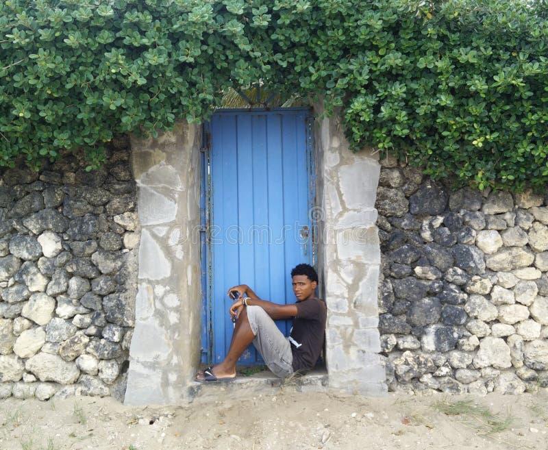 Неизвестный человек сидя на двери стоковая фотография rf