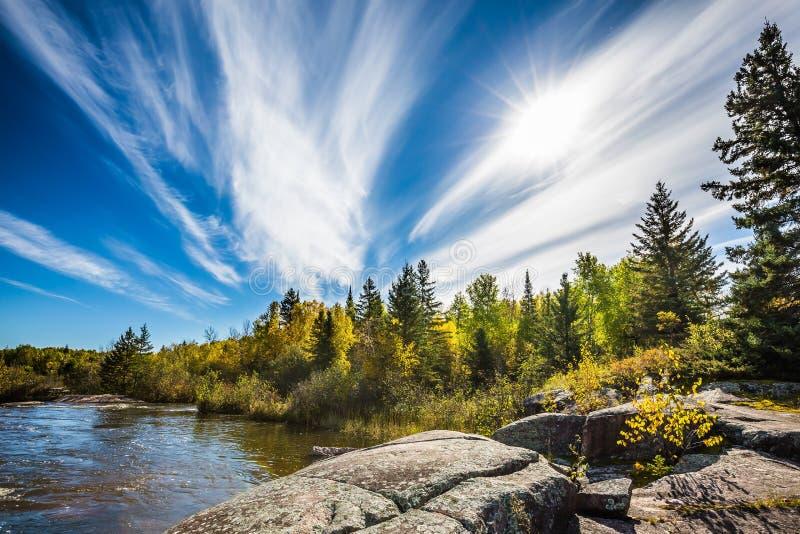 Неимоверные облака цирруса и огромные плоские камни в старом парке запруды Pinawa Бабье лето в Манитобе, Канаде Концепция  стоковая фотография rf