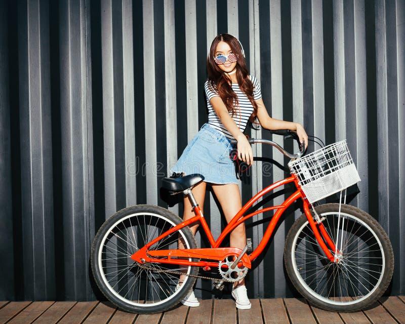 Неимоверный длинн-шагающий азиат девушки в обмундировании лета, американских солнечных очках, игроке кассеты и наушниках представ стоковое изображение rf