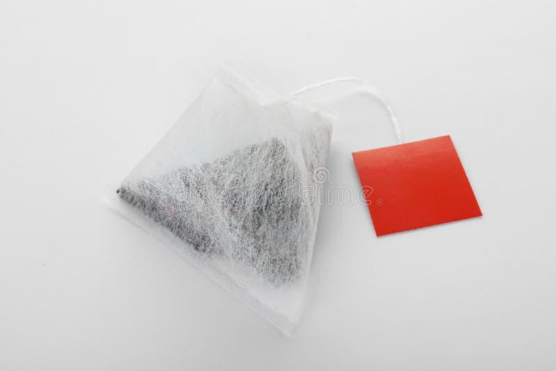 Неиспользованный пакетик чая пирамиды с биркой на белизне Космос для текста стоковое фото