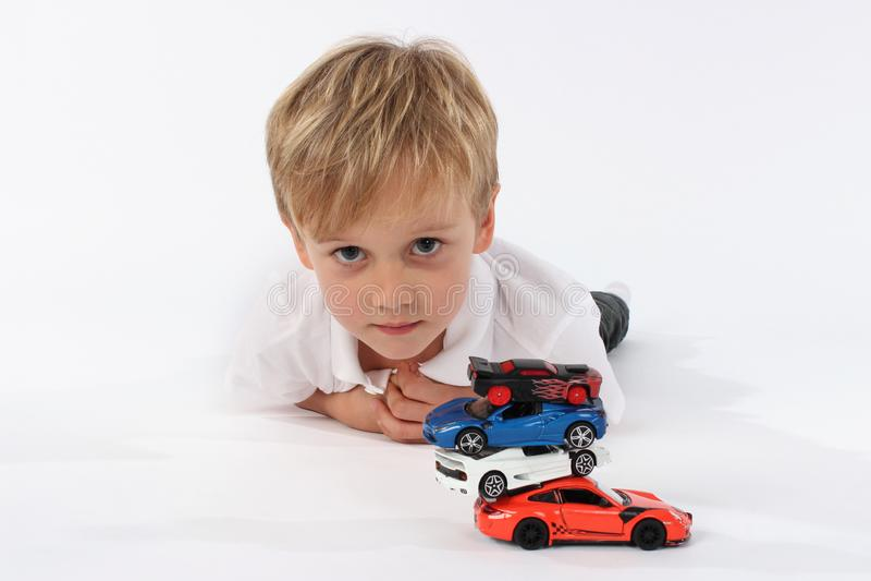 Нейтральный и невиновный взгляд ребенка детского сада после игры с игрушками автомобиля стоковые изображения rf